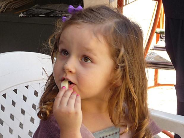Nina come uma maça enquanto espera a mamãe (Foto: Avenida Brasil / TV Globo)