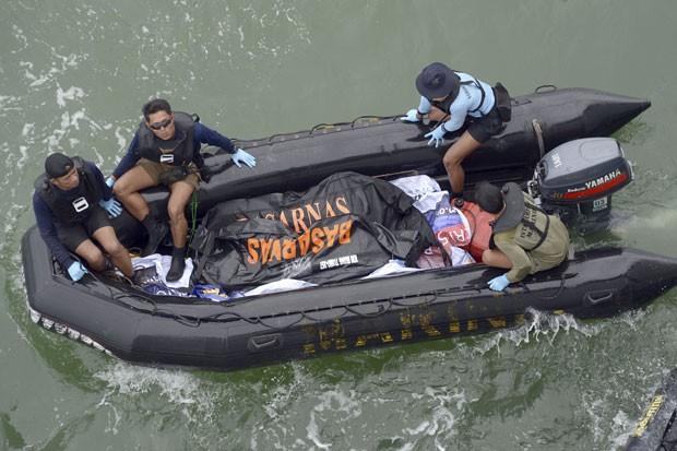 Equipe da Marinha da Indonésia carrega corpo de vítima do acidente da AirAsia em barco neste sábado (3) (Foto: Adek Berry/AP)