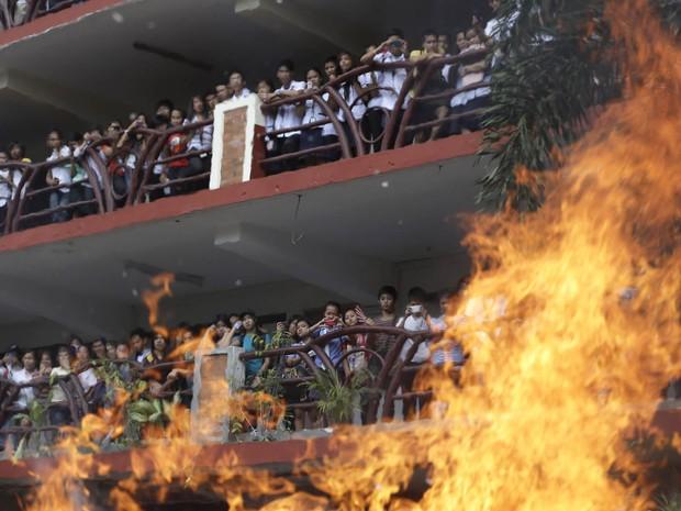 Estudantes da Universidade Politécnica das Filipinas queimam cadeiras velhas e monitores de computador durante um protesto em apoio a um calouro de 16 anos da universidade, que cometeu suicídio há três dias. (Foto: Bullit Marquez/AP)