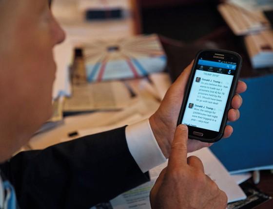 Trump com seu celular que usa para tuitar.Ele dissemina informações de veracidade questionável (Foto: osh Haner/The New York Times)