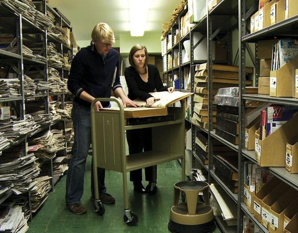 NO ACERVO: O diretor Joel Allen Schroeder manuseia as tiras originais de Bill Watterson (Foto: divulgação)