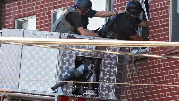 Antes de entrar no local, policiais utilizam uma câmera para verificar a casa do suspeito pelo tiroteio em Aurora, Colorado (Foto: Ed Andrieski/AP)
