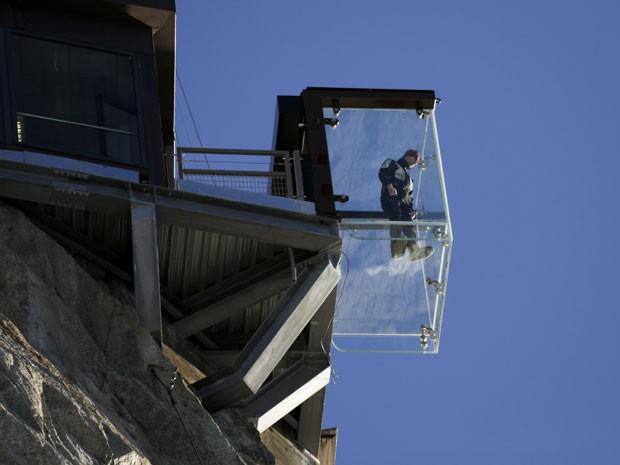 Homem fica em pé na cabine de vidro no alto da montanha (Foto: Robert Pratta/Reuters)