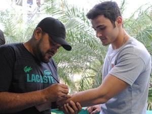 Sérgio retoca a tatoo do ator antes de entrar em cena (Foto: Malhação / Tv Globo)