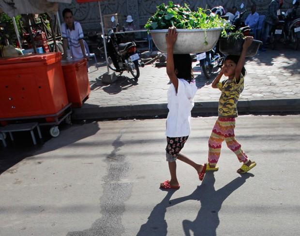 Meninas carregam vegetais perto de um mercado na vila de Chroy Changvar, em Phnom Penh (Foto: Heng Sinith/AP)
