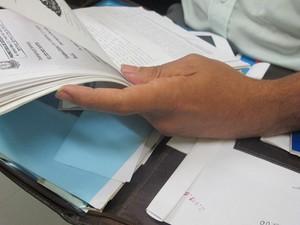 Pai guarda documentos e folhas do processo sobre o assassinato do filho (Foto: Nathália Duarte/G1)