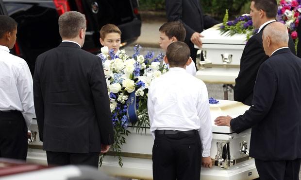 Crianças são vistas ao lado dos caixões da família Stay durante enterro nesta quarta-feira (16) (Foto: David J. Phillip/AP)