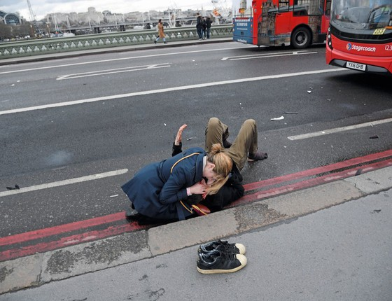 Uma mulher socorre vitima do atentado.reino Unido tem um dos serviços de intelig~encia mais eficientes do mundo (Foto: Toby Melville / Reuters)