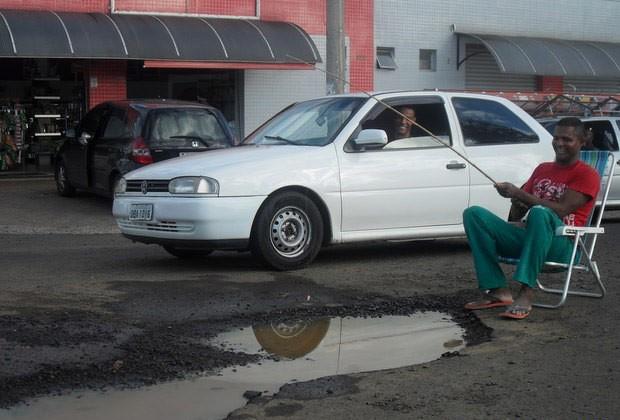 Homem ironiza buraco de rua sem reparo em Piracicaba (Foto: Carlos Eduardo da Silva/VC no G1)