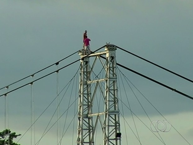Jovens foram flagrados se arriscando no topo de ponte para tirar selfies, em Goiás (Foto: Reprodução/TV Anhanguera)
