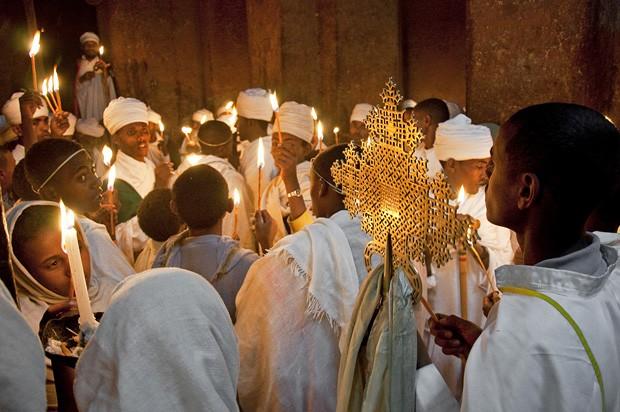 No interior de Bet Mikael, diáconos e sacerdotes acendem velas para uma vigília noturna. Uma cruz de procissão de bronze abençoa os devotos (Foto: © Haroldo Castro/Época)