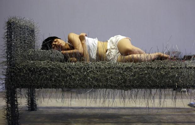 Artista Zhou Jie tira soneca em sala de exposições em Pequim (Foto: Jason Lee/Reuters)