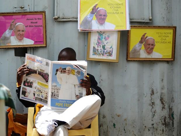 Um homem lê o jornal 'Catholic Mirror', cercado por fotos do Papa Francisco, em Nairobi, no Quênia, na segunda (23) (Foto: AFP Photo/Tony Karumba)
