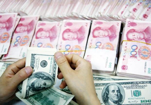 Funcionário conta notas de yuan e dólares em uma filial do Banco Comercial e Industrial da China em Huabei, província da China ; câmbio na China ; (Foto: ChinaFotoPress/Getty Images)