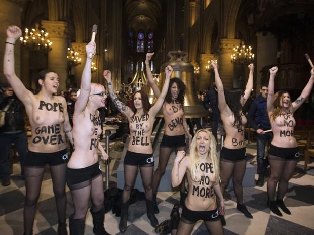 Feministas dentro da catedral de Notre Dame, em Paris, festejam a renúncia do Papa Bento XVI (Foto: AFP/Joel Saget)