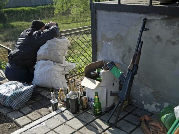 Ativista pró-Rússia guarda um posto de controle em uma ferrovia perto da cidade de Slaviansk, no leste da Ucrânia. (Foto: Baz Ratner / Reuters)
