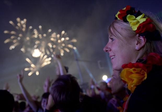 Fogos iluminam o céu enquanto torcedora comemora vitória da Alemanha na Copa do Mundo nesta segunda-feira (14) em Berlim (Foto: Britta Pedersen/AP)