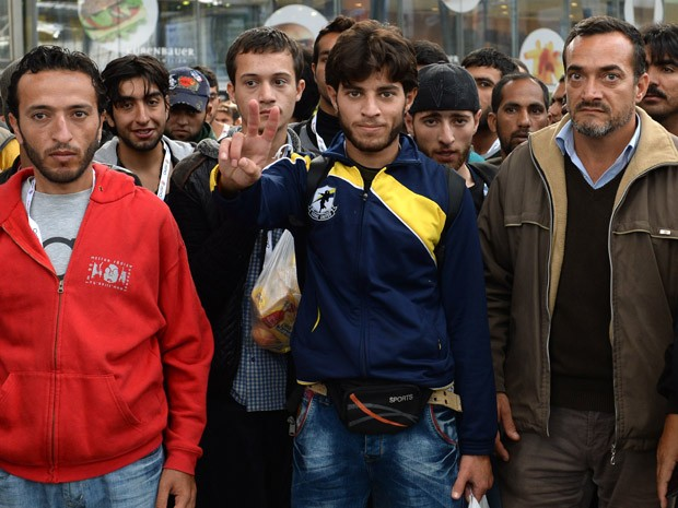 Refugiados esperam por um trem especial na principal estação ferroviária de Munique, neste domingo (13) (Foto: AFP PHOTO/CHRISTOF STACHE)