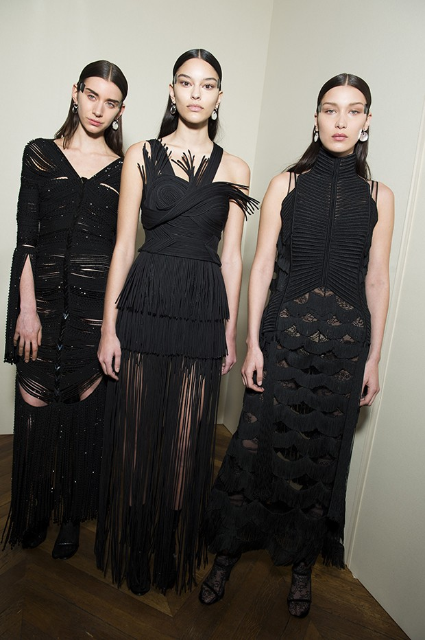 From left: Juliette wears a matte-black jersey tube dress embellished all over with shiny black beads and mirror-effect crystals; Elizabeth wears a sculpted dress made of juxtaposed organza tubes appliquéd on a tulle bustier decorated with macramé fringes; Bella Hadid wears an embellished illusion-tulle dress with a silk-embroidered front and graduated fringes on an organza base, worn with a lace-encrusted jumpsuit. (Foto: Givenchy)