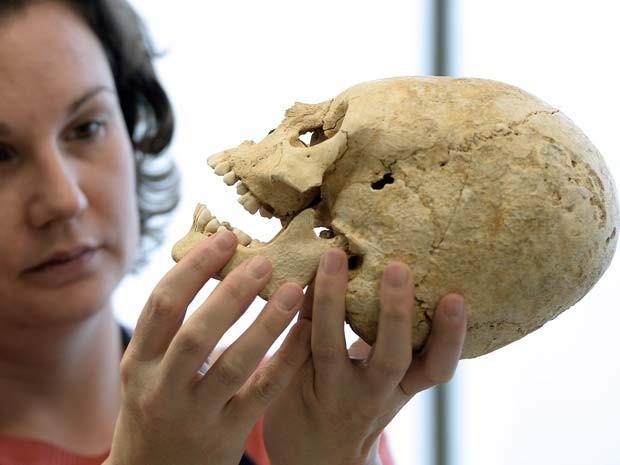 Pesquisadora de instituto de arqueologia francês trabalha no crânio deformado encontrado (Foto: FREDERICK FLORIN / AFP)