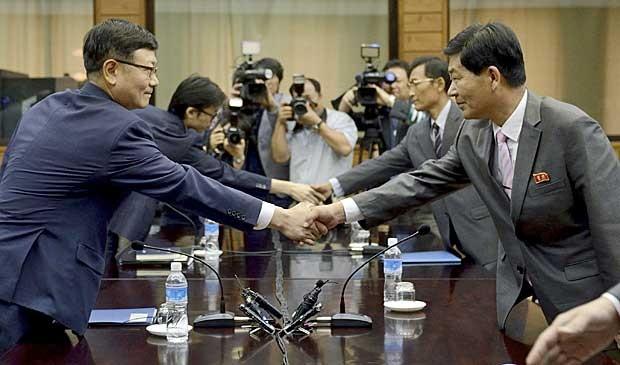 Suh Ho, o chefe da delegação de trabalho da Coreia do Sul, aperta a mão do norte-coreano Parque Chol Su, durante iniício de reunião em Tongilgak, no lado norte-coreano de Panmunjom. (Foto: Yonhap / AP Photo)