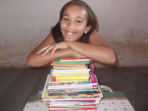 Clara apresenta os livros que já leu em sua casa (Foto: Patricia Carvalho / G1)