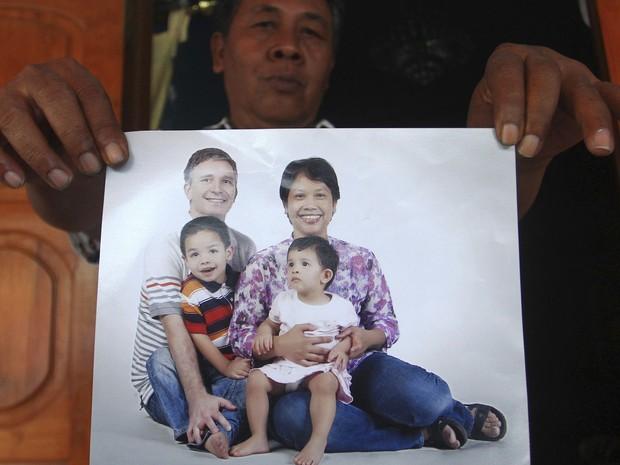 Widi Yuwono mostra foto da irmã Yuli Hastini com o marido holandês John Paulissen e os filhos Arjun e Sri. Os quatro embarcaram em Amsterdã no voo MH17 (Foto: AP)