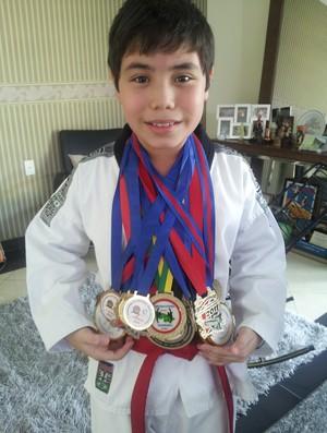 Atleta acreano de 10 anos mostra medalhas conquistadas no taekwondo (Foto: João Paulo Maia)