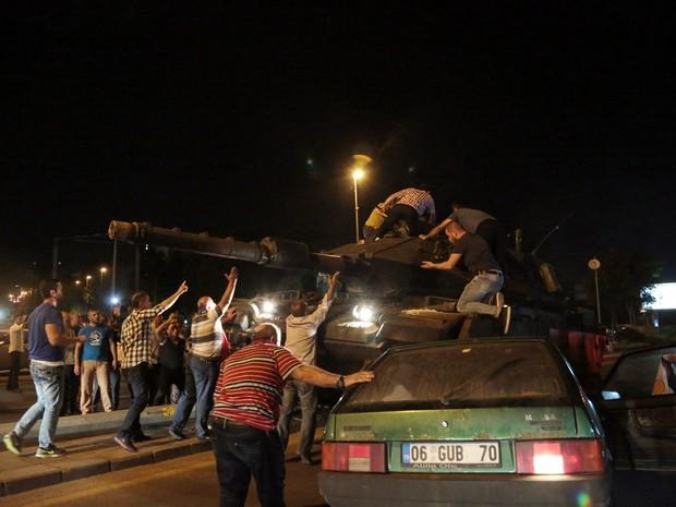 Pessoas que protestam nas ruas sobem em tanques que se movem para tentar detê-los em Ancara, na Turquia (Foto: Burhan Özbilici/AP)