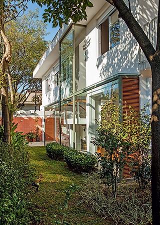 Os arquitetos criaram uma caixa de vidro que avança no jardim lateral para aumentar a largura do living (Foto: Edu Castello/Casa e Jardim)