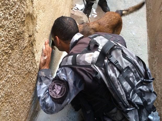 PM do BAC olha dentro de buraco na parede ao lado de cão (Foto: Divulgação / BAC)