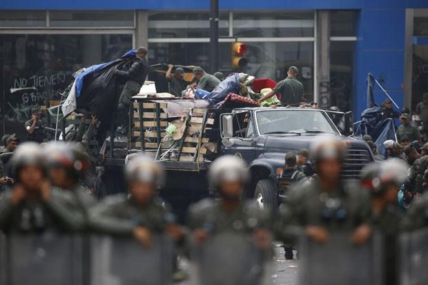 Integrantes da Guarda Nacional Bolivariana  desmontam acampamento de estudantes na Venezuela nesta quinta-feira (8) (Foto: Carlos Garcia Rawlins/Reuters)