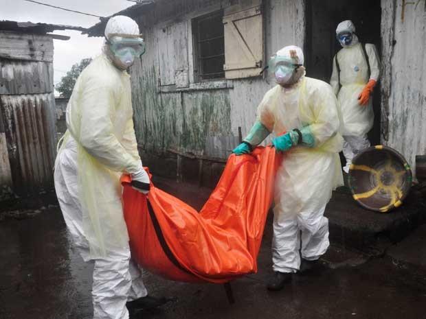 Enfermeiros se protegem ao carregar o corpo de uma mulher suspeita de ter morrido após contrair de vírus Ebola. (Foto: Abbas Dulleh / AP Photo)