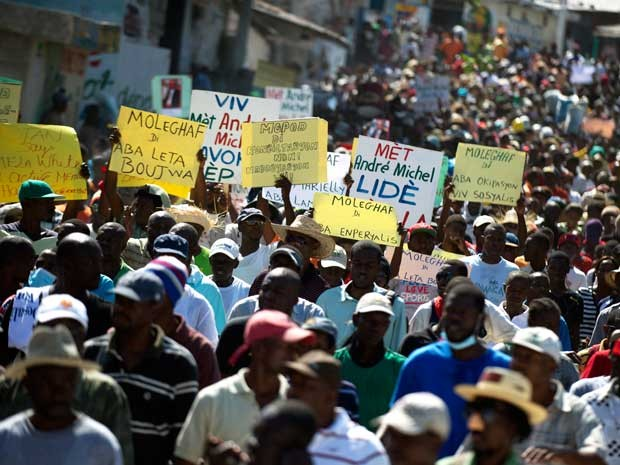 Manifestantes marcham em porto Príncipe durante protesto contra o governo do presidente Michel Martelly. (Foto: Hector Retamal / AFP Photo)