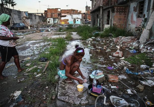 Jovem Alessandra lava utensílios de cozinha com mangueira em meio a ruínas de casas na comunidade Metro-Manguera, no Rio de Janeiro ; pobreza ; favela ;  (Foto: Mario Tama/Getty Images)