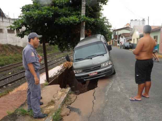 Van ficou pendurada após asfalto ceder na Rua João Aprigio Costa, no bairro de Santa Terezinha, em Aparecida (SP). (Foto: Talita Gabrielle)