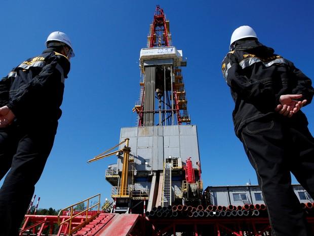 Trabalhadores observam plataforma de perfuração na Rússia (Foto: Sergei Karpukhin / Reuters)