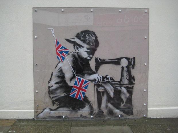 Mural pintado por Banksy numa loja no norte de Londres durante o jubileu de diamante da rainha, em 2012; a obra teria sido posteriormente 'roubada' em fevereiro de 2013 (Foto: Haringey Council/AP)