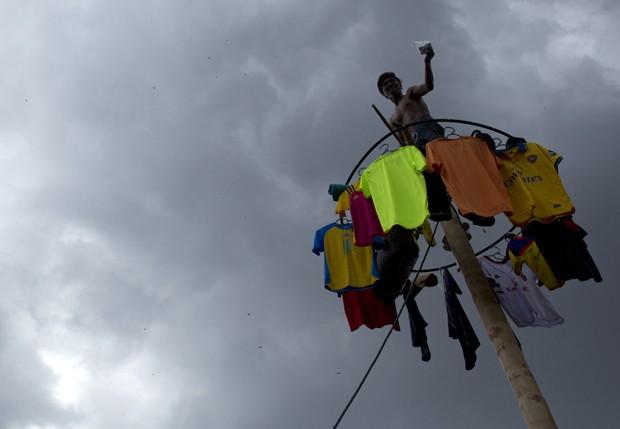 Homem comemora prêmio ao conseguir escalar pau de sebo em competição na Malásia. Participantes que chegam ao topo ganham prêmios como dinheiro e roupas (Foto: Mohd Rasfan/AFP)