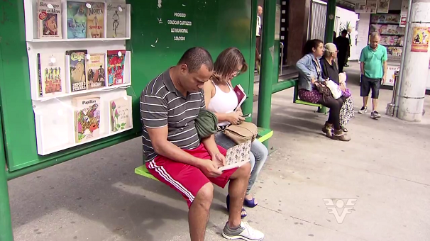 Pessoas pegam os livros para a distração no ponto de ônibus (Foto: Reprodução/TV Tribuna)