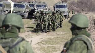 Soldados, que seriam russos, do lado de fora do território de uma unidade militar ucraniana no vilarejo de Perevalnoy, na Crimeia (Foto: Reuters)