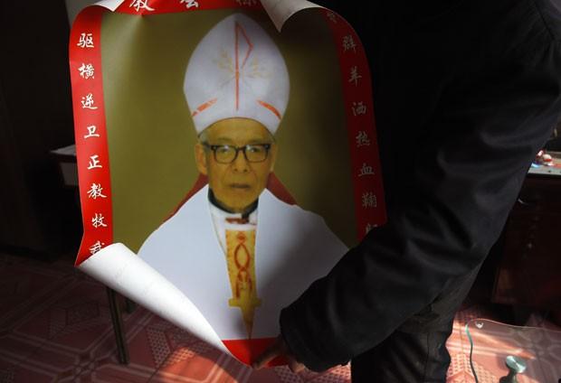 Parente do bispo católico Shi Enxiang mostra foto do religioso nesta terça-feira (24) em Shizhuang, na China (Foto: Greg Baker/AFP)