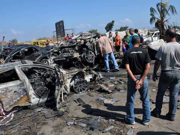 Homens observam destroços de carro em local onde houve explosão no Líbano. (Foto: Ibrahim Chalhoub/AFP)