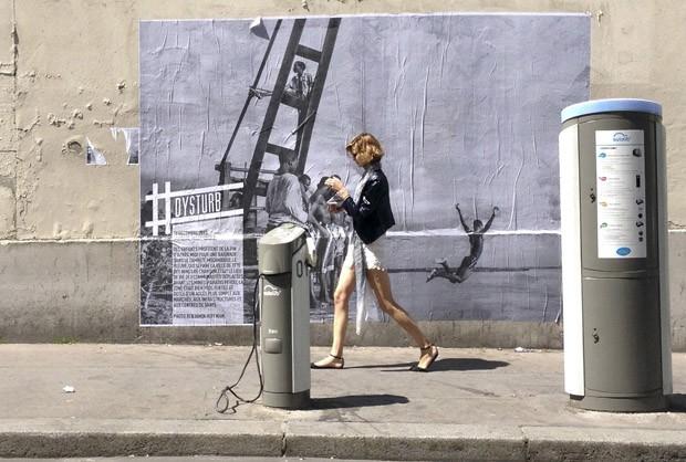 Mulher passa por uma foto de Benjamin Hoffman feita em Moçambique colada em rua de Paris (Foto: Francois Mori/AP)