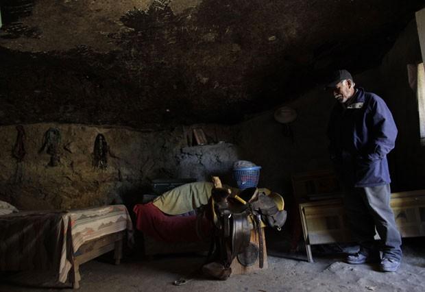 Benito mostra o interior de seu lar, onde parte das paredes e o teto são a própria rocha escavada (Foto: Daniel Becerril/Reuters)