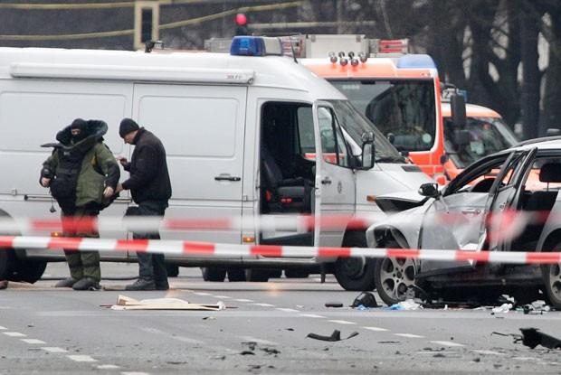 Especialista de esquadrão antibomba coloca equipamentos de proteção ao lado de carro que explodiu em Berlim, na Alemanha, nesta terça-feira  (Foto: Michael Sohn/AP)