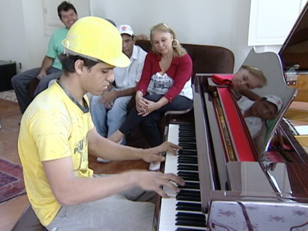 Trabalhadores e moradores da casa de reúnem para ouvir as músicas tocadas pelo pedreiro, em Vitória (Foto: Reprodução/TV Gazeta)