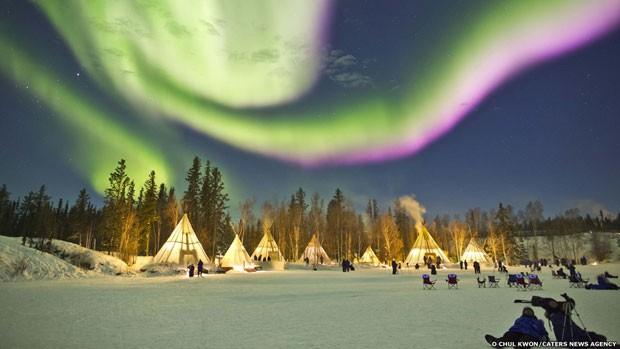 Todo ano, milhares de turistas viajam para a capital do Território Noroeste do Canadá para tentar aproveitar essa visão espetacular.  (Foto: O Chul Kwon/Caters News)