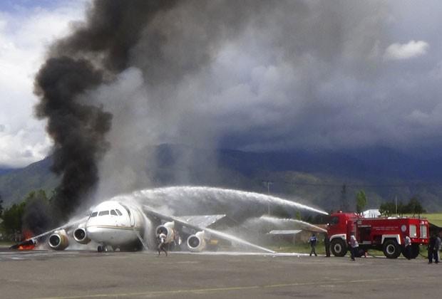 Bombeiros tentam combater chamas em avião na Indonésia (Foto: AP)