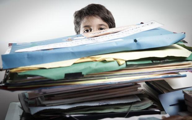 João Victor, aluno do 4º ano, mostra pilha de material produzido desde a pré-escola no acervo de sua casa (Foto: Caio Kenji/G1)